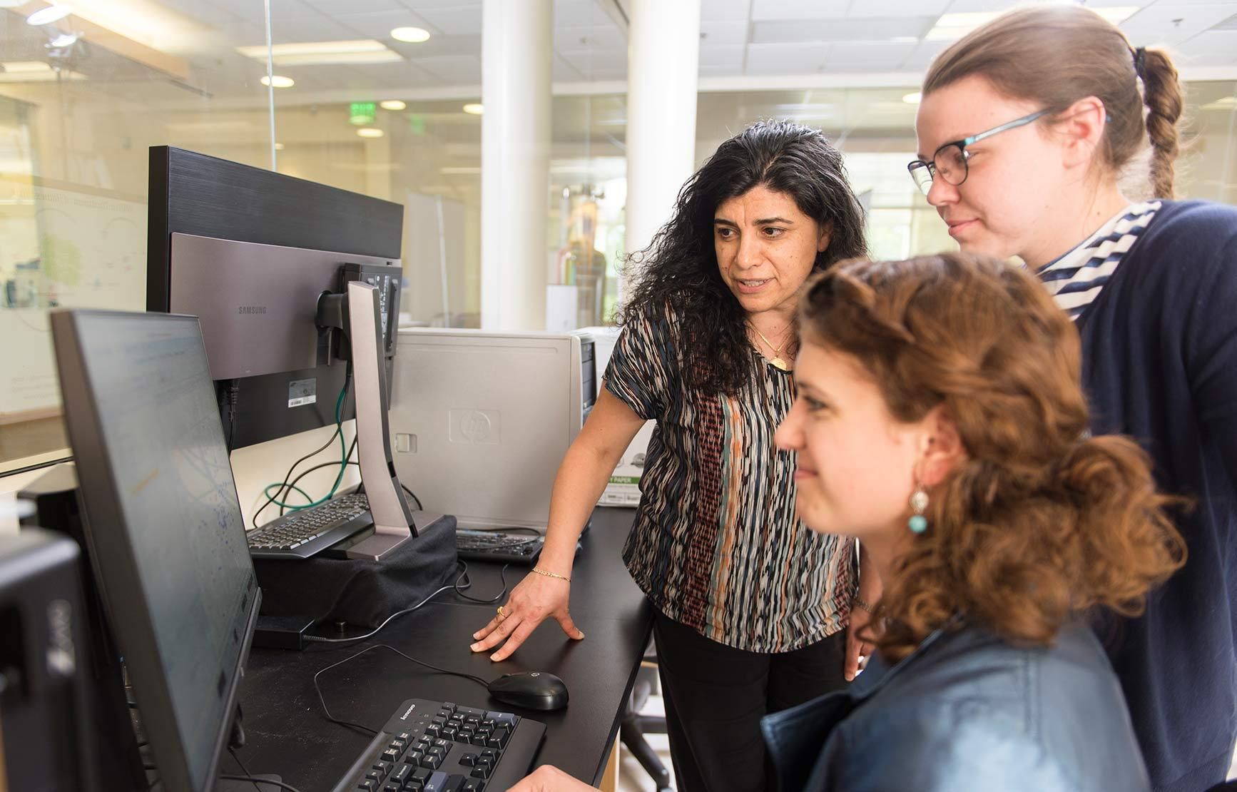 female professor and students working together on lab assignment