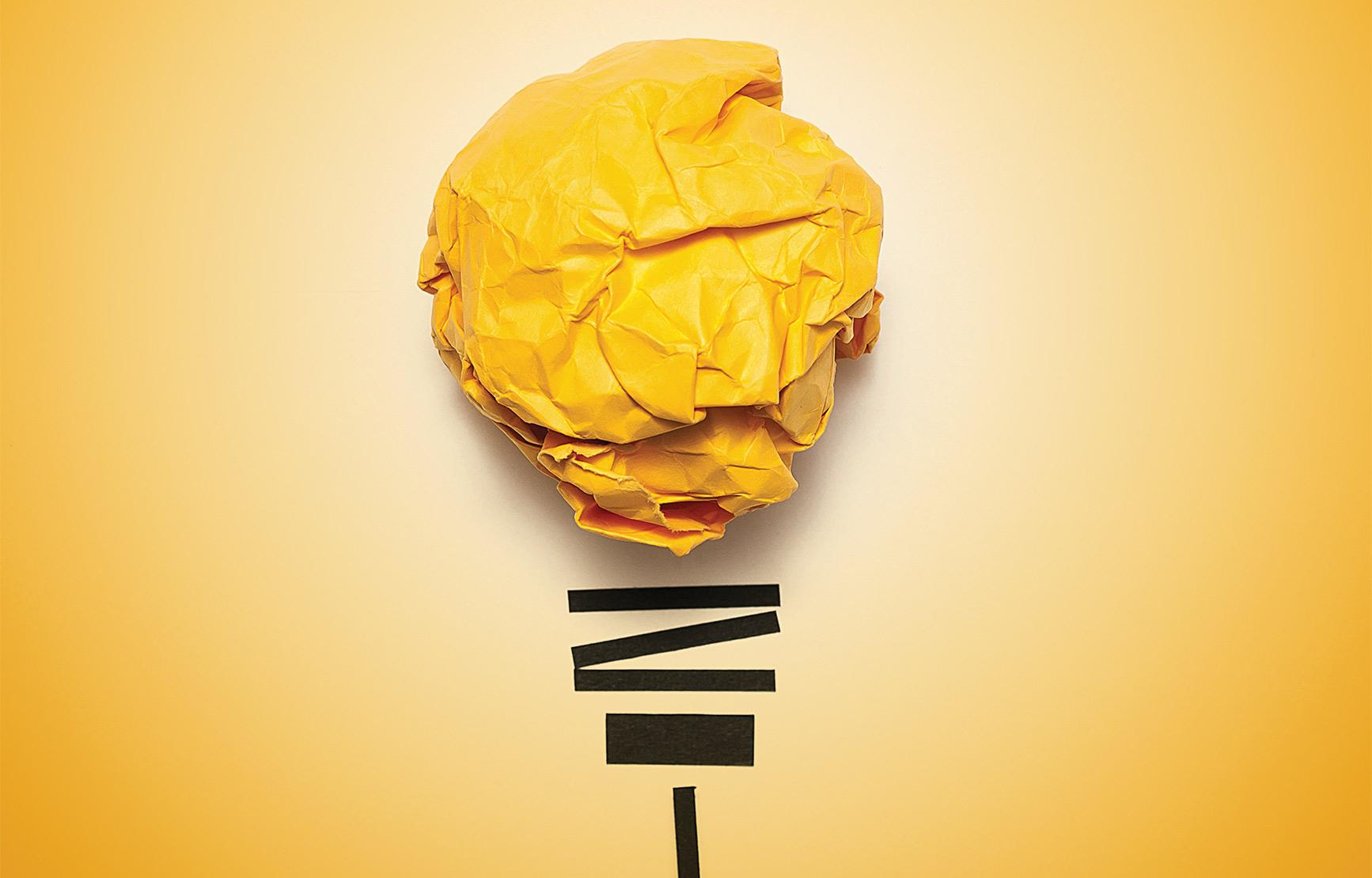 yellow crumpled paper and tape modeled as light bulb in front of yellow backdrop