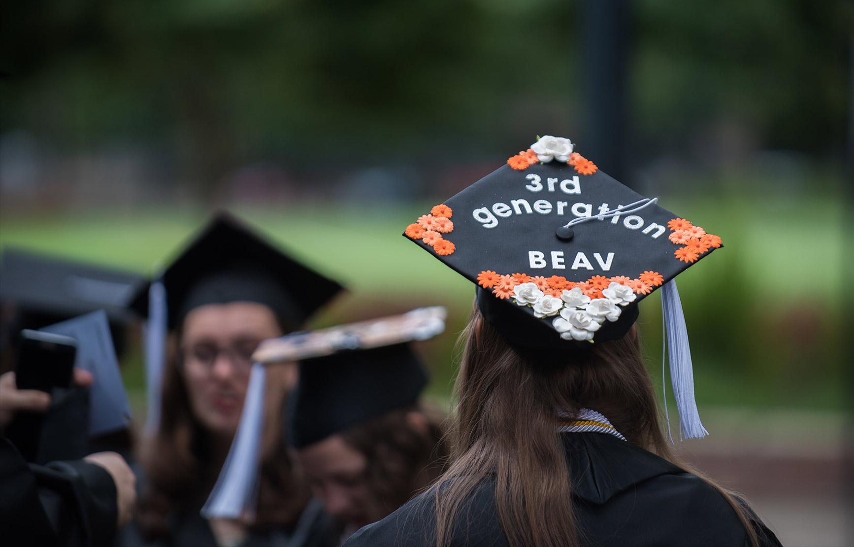 """Graduating student in crowd of graduates, wearing a grad cap with """"3rd generation BEAV"""" written on with flower decorations."""