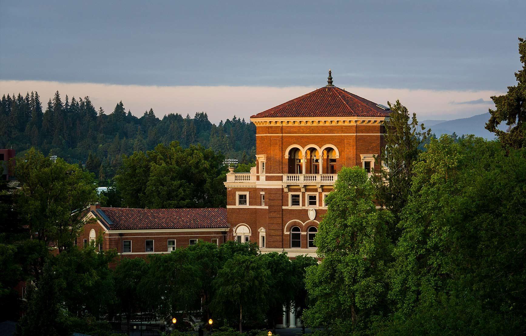 Weatherford Hall peering through trees during sunset.