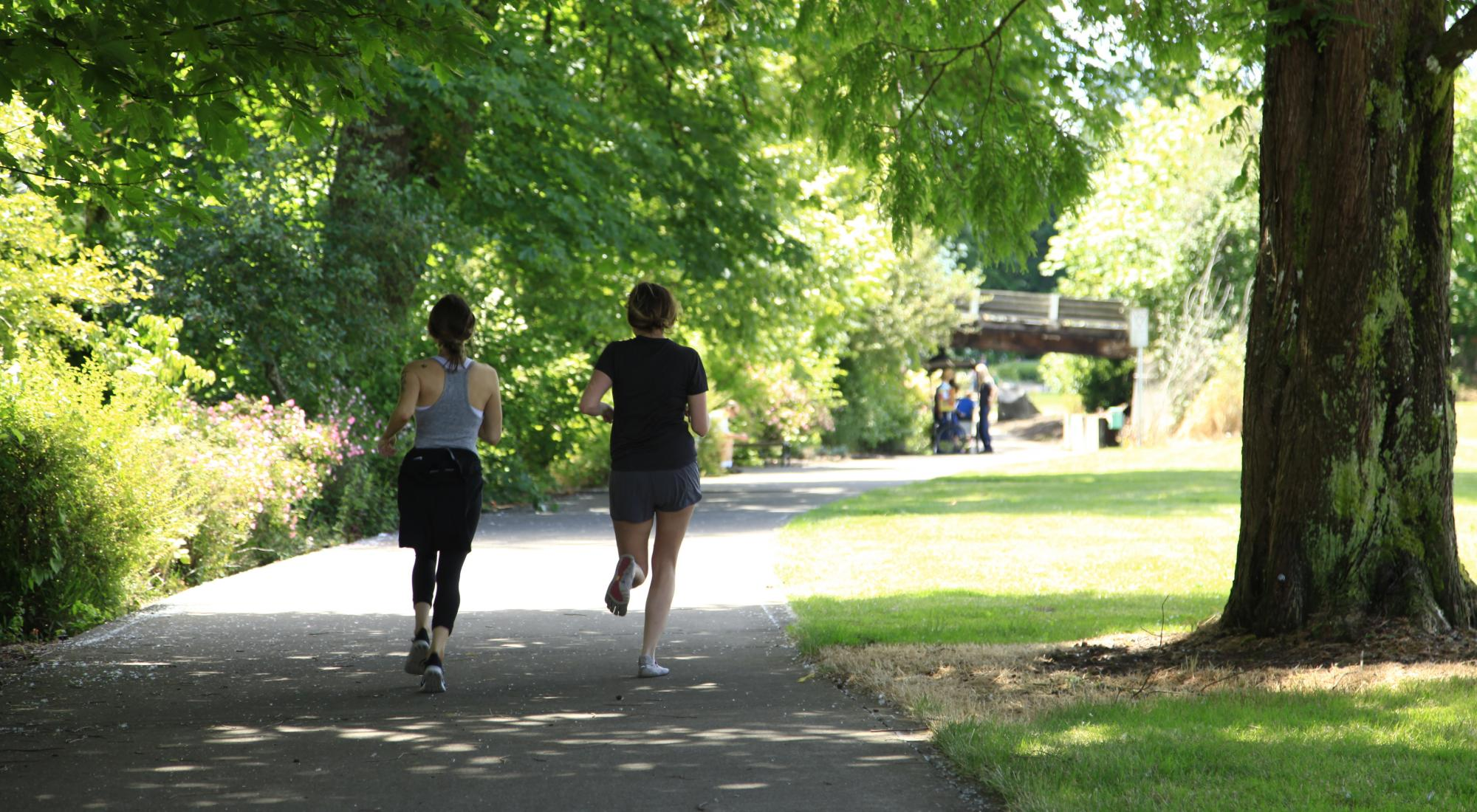 Two women running in downtown Corvallis, surrounded by lush trees