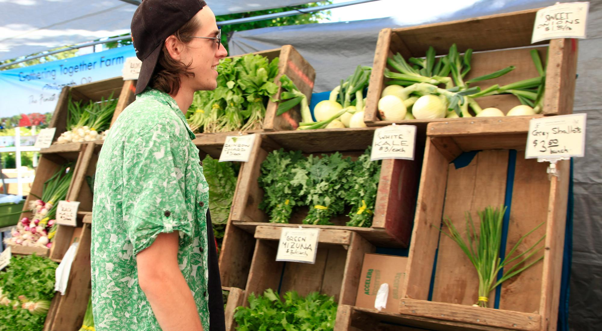 A young man considering produce at the farmer's market