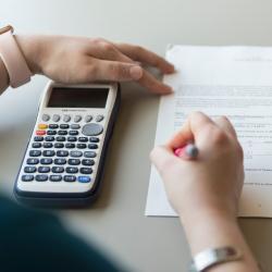 student working on math homework holding calculator