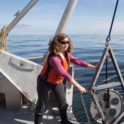 Sarah Henkel on a boat working with marine research machinery