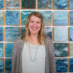 Abigail Losli standing in front of her paintings