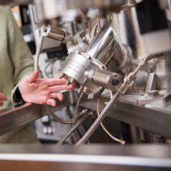 Janet Tate pointing to material science machinery