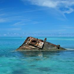 sunken ship peering above surface of ocean on a sunny day