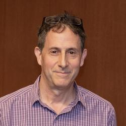 Mike Lerner in front of wooden backdrop