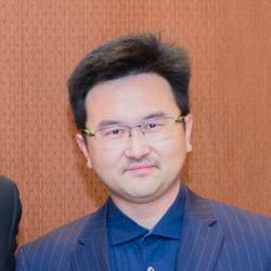 David Xiulei Ji in front of wooden backdrop