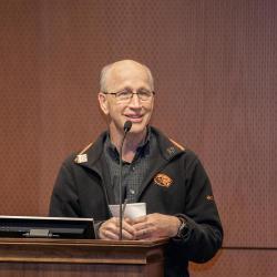 Andy Karplus talking behind podium