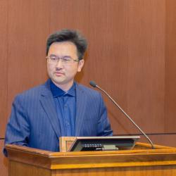 David Ji talking behind podium