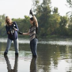 Kim Halsey with graduate student taking samples from a river