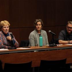 Jane, Karen, and Steve sitting behind panel table, talking into microphones