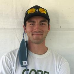 Zack Bango smiling in front of a white background, wearing a CORE shirt