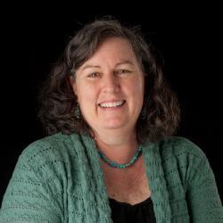 Margie Haak standing in front of black backdrop