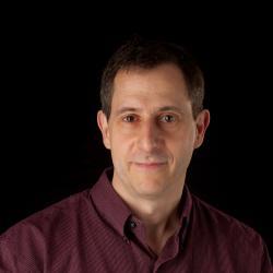 Michael Lerner standing in front of black backdrop