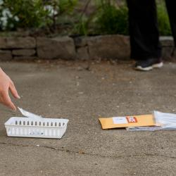 Corvallis resident placing COVID test in tray on sidewalk for TRACE field staff worker to collect.