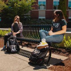 students in masks sit on a bench on OSU's campus