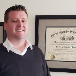 Scott Rennie standing in front of plaque.