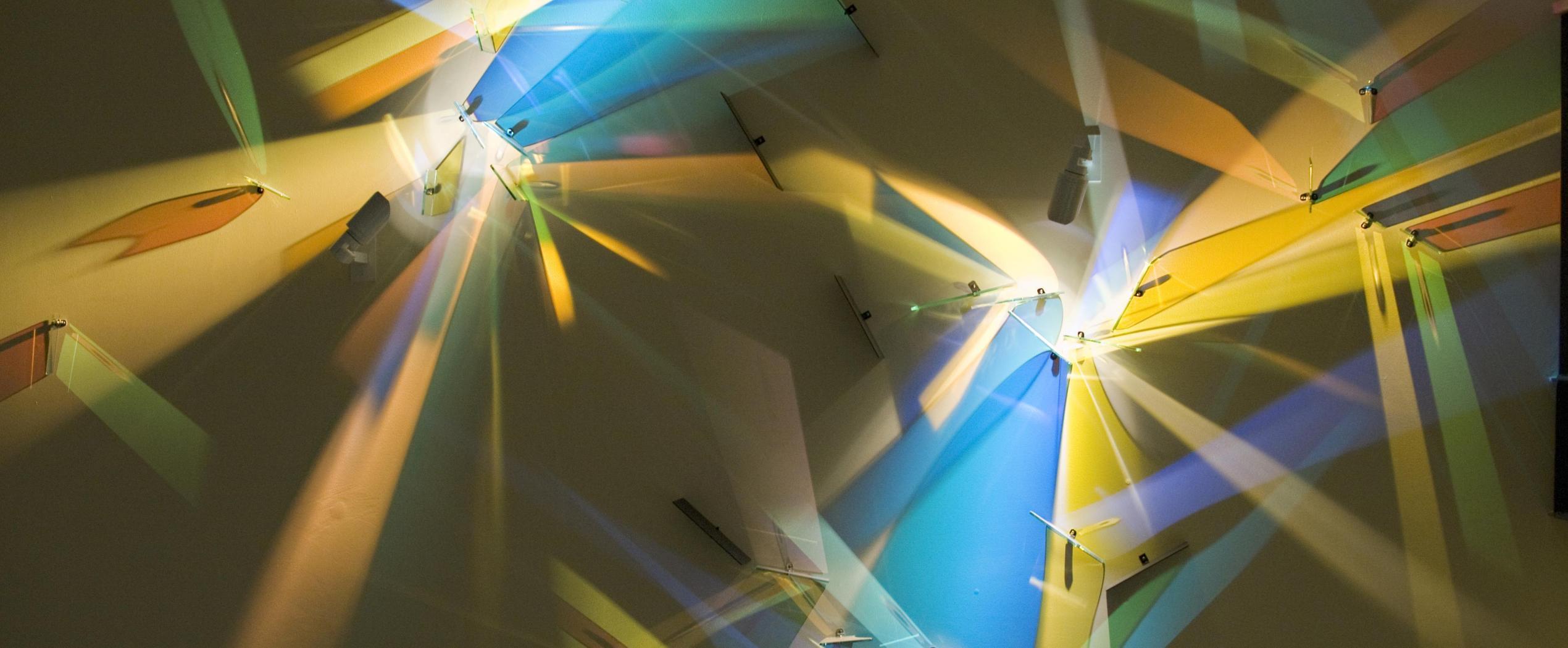 Glass art piece reflecting light from wall