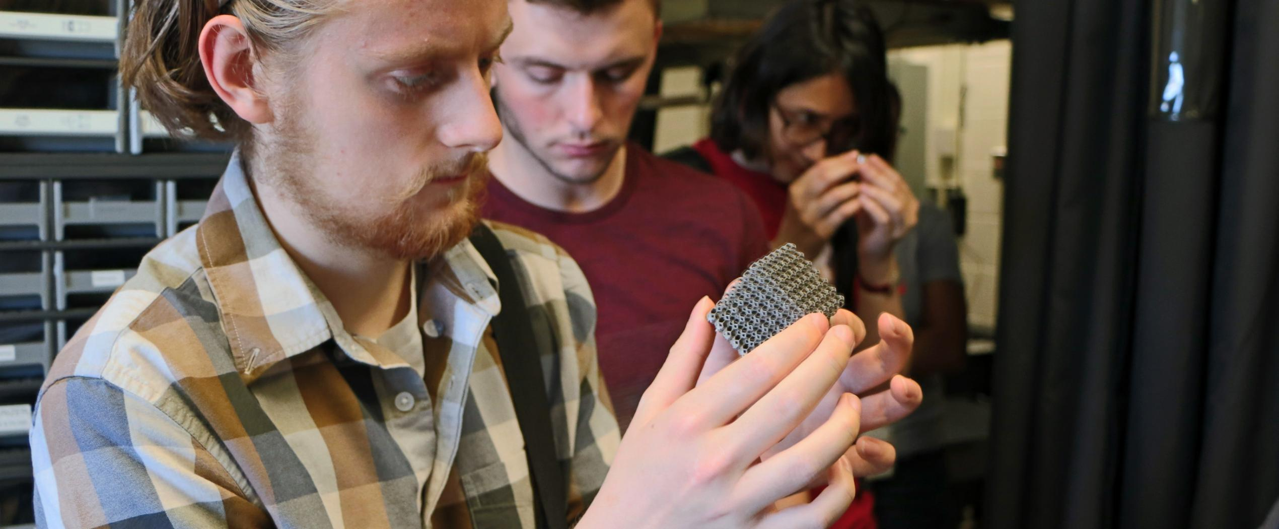 Student examining 3D printed metal structure