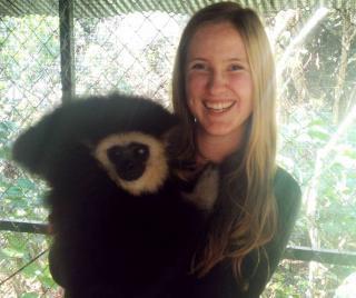 Karianna Crowder holding a white-cheeked gibbon in enclosure