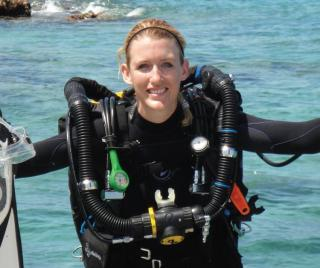 Megan Cook in scuba gear climbing into boat