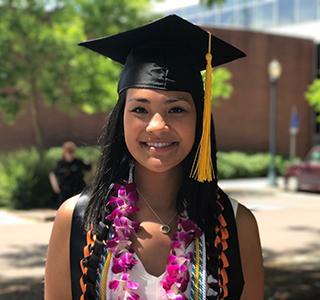 Chloe Villagomez standing on campus wearing Graduation cap