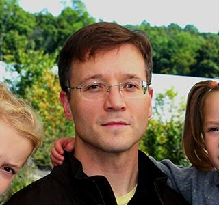 Justin Hall in garden holding daughters in arms