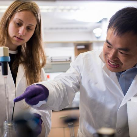 Weihong Qiu pointing at samples with female mentee, Haelyn Epp, in lab
