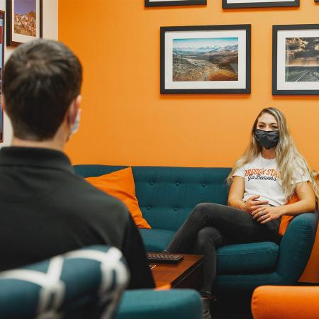 A student and mentor engage wearing masks in the physical-distancing environment