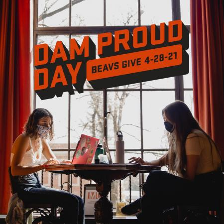 Dam Proud Day logo above an image of two students studying in the Memorial Union lounge.