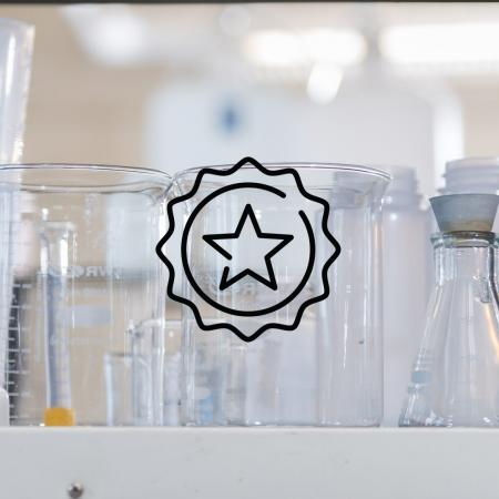 A star badge icon above an image of beakers and lab equipment sitting on a lab table.