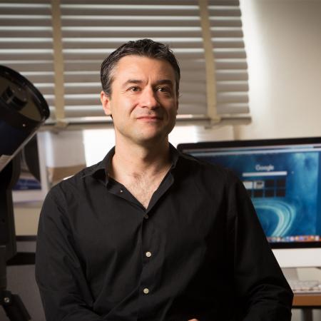 Davide Lazzati sitting in office.