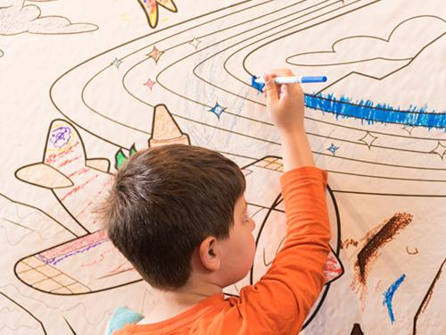 Child drawing with crayon on coloring book paper wall