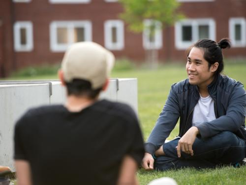 students sitting on Austin Hall lawn