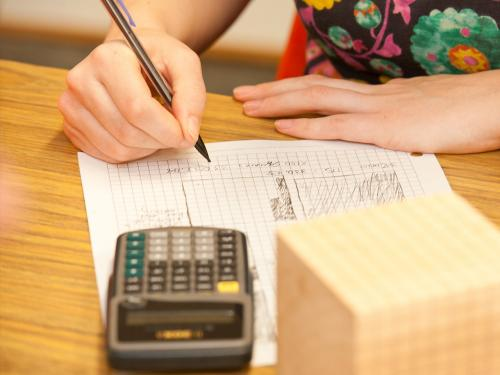student working on mathematics homework at desk with calculator and wooden cube.