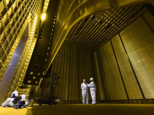 two researchers standing in golden electric field cage facility.