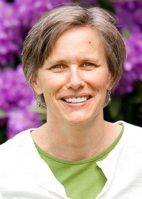 Alix Gitelman in front of flowery bush