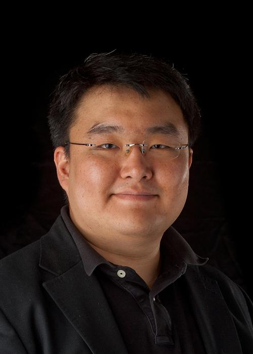 Paul Cheong in front of black backdrop