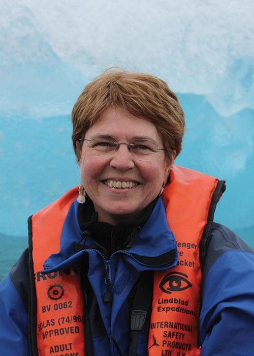 Jane Lubchenco in front of ice glacier wearing life jacket