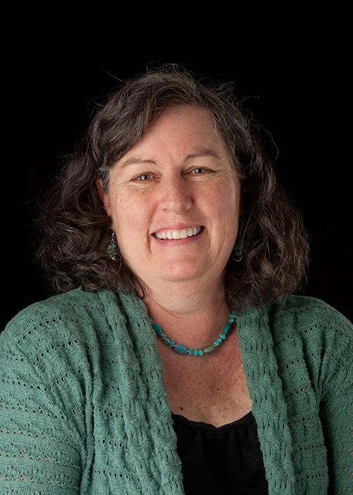 Margie Haak in front of black backdrop