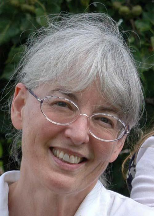 Lynn Houck in front of shrubbery
