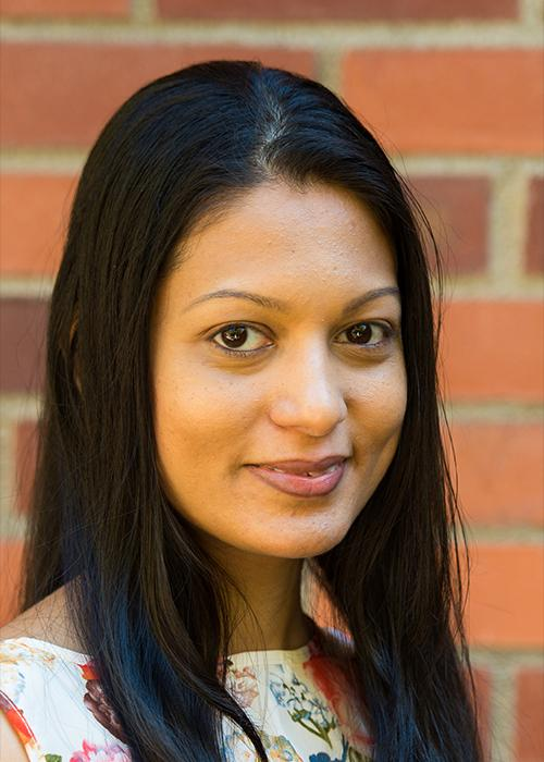 Sulochana Wasala standing in front of a brick wall.