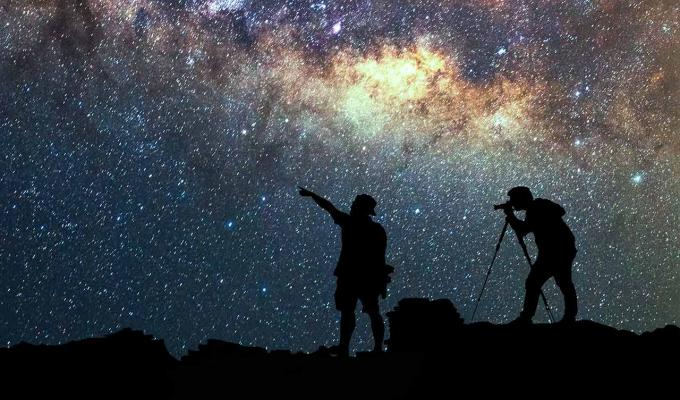 two silhouetted people watching the stars