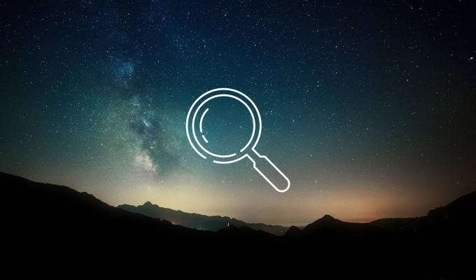 magnifying glass icon above image of mountain ridge at night