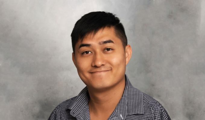 Stanley Yu smiling in front of a gray background