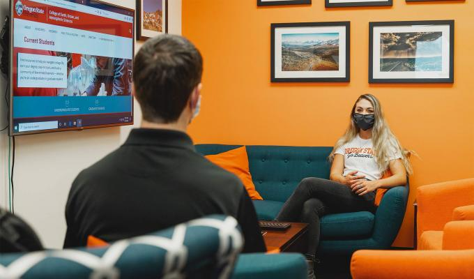 A student and mentor engage wearing masks in the physical-distancing environment.
