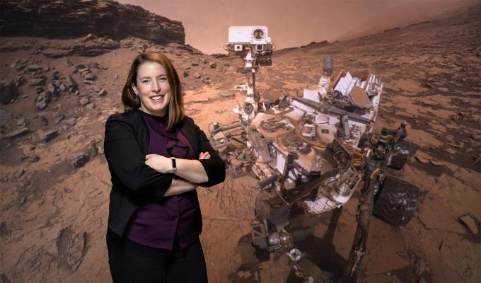Planetary geologist and OSU alumna Briony Horgan in front of an image of the Perseverance rover.