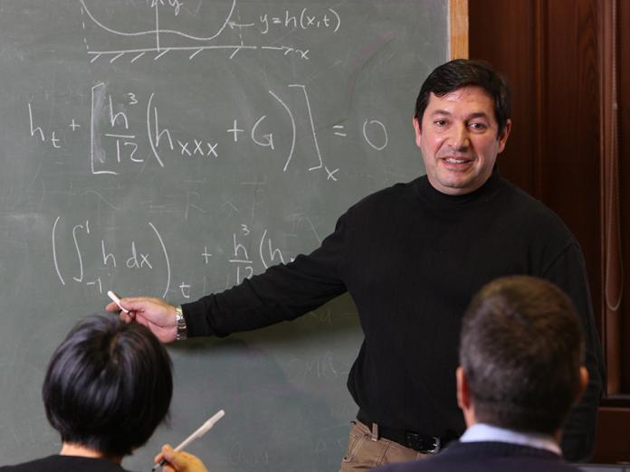Juan Restrepo showing equation to colleagues on chalkboard
